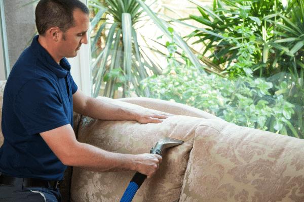 איש מבצע ניקוי לספה עם מכונה